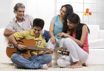 Boy playing the guitar for his family