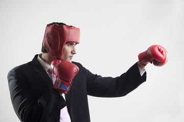 Businessman with boxing gloves punching