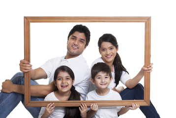 Portrait of happy family holding frame