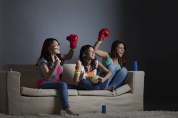 Cheerful young female friends watching boxing match together at home