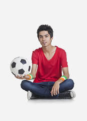 Portrait of young boy in casual wear holding soccer ball over white background