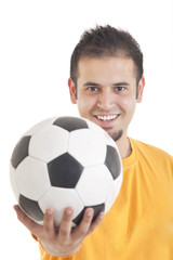 Portrait of young man smiling while holding soccer ball over white background