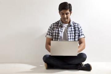 Full length of handsome man using laptop