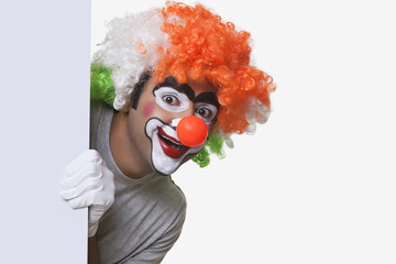 Male clown in tricolor wig smiling over white background