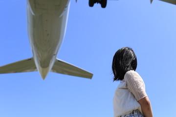 飛行機を眺める女性