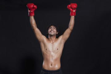 Male boxer celebrating victory on black background