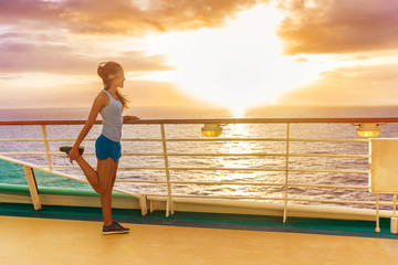 Wall Mural - Cruise ship vacation healthy active running lifestyle. Fitness runner woman stretching leg warm-up before exercise on outdoor deck of cruise ship boat. Woman enjoying Caribbean holiday.