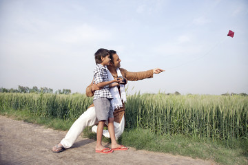 Happy father and son flying a kite in field