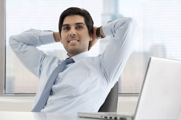 Relaxed young businessman sitting at his desk with laptop