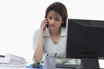 Angry businesswoman on call while using computer