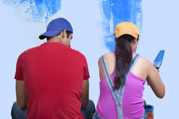 Rear view of young couple sitting with incomplete painted wall