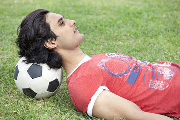 Handsome young man lying on back with head on soccer ball