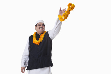 Smiling politician throwing garland
