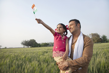 Man with his daughter holding Indian flag in an agricultural field