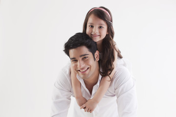 Portrait of adorable girl sitting on her father's back