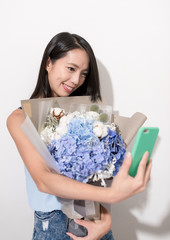 Woman holding flower to take selfie