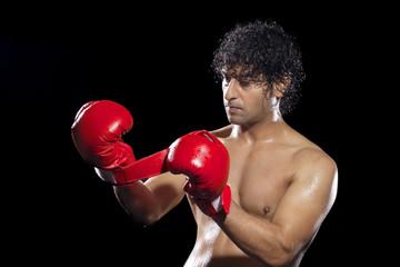 Boxer wearing gloves over black background