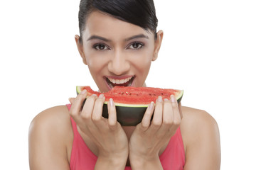 Portrait of beautiful young woman biting slice of watermelon