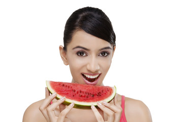Close-up portrait of smiling young woman with a slice of watermelon