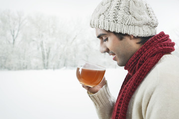 Young man drinking black tea during winter