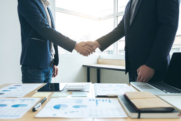 Two business men shaking hands during a meeting to sign agreement and become a business partner, companies, confident, success dealing, contract between their firms