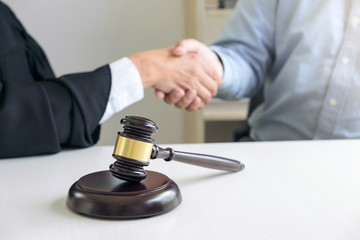 Image of hands, Male lawyer or judge and client shaking hands on table after good deal in modern office Near gavel, Concept of legal services, law, legal advice