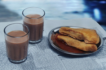 Glasses of chai and plate of snack on newspaper