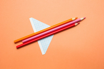 Aircraft made of pencils and paper on an orange background. Back to school.