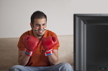 Young man in casuals with face painted wearing boxing gloves watching television at home