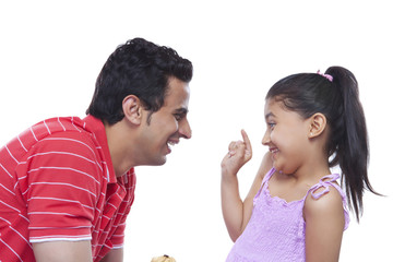 Playful daughter putting cream on father's nose over white background