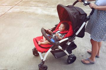 happy baby boy cute in child stroller seat on wheel