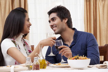 Couple looking at each other while clinking wine glass at restaurant
