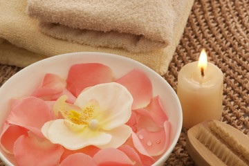 Rose petals and orchid in a bowl with nail brush