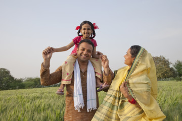 Portrait of a cheerful rural family in the field