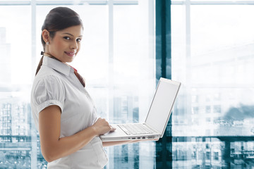 Portrait of young businesswoman smiling with laptop at office