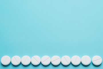 A row of white pills on a blue surface.Copy space