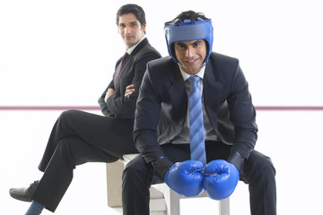 Portrait of businessman with boxing gloves sitting on a bench