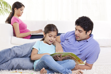Father helping child in homework with woman using laptop in the background