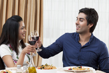 Happy young couple clinking wine glass during meal