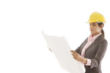 Female engineer reading blueprints