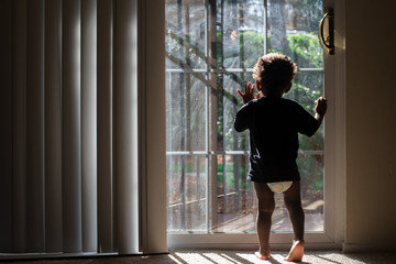 toddler  faces window to outdoors