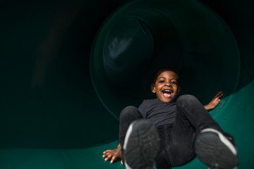Boy laughing while playing on slide