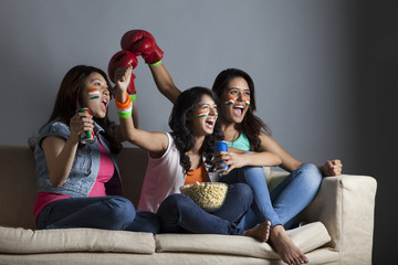 Excited young female friends watching boxing match together at home