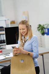 frau sitzt am schreibtisch und schaut auf ihr mobiltelefon