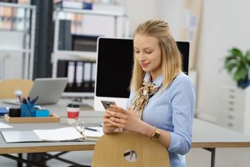 angestellte im büro liest eine nachricht am handy