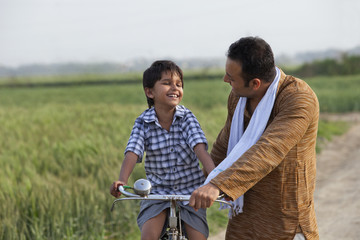 Man teaching son to ride bicycle