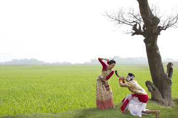 Bihu man blowing on a pepa while Bihu woman dances to his tune