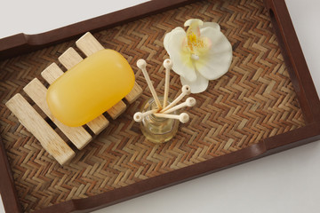 Soap , reed diffuser and orchid in a tray