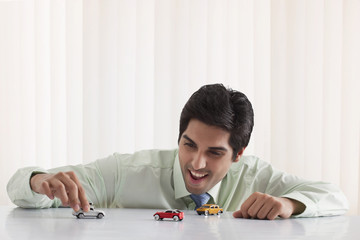 Happy businessman playing with model car