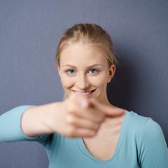 glückliche junge frau zeigt mit dem finger nach vorn